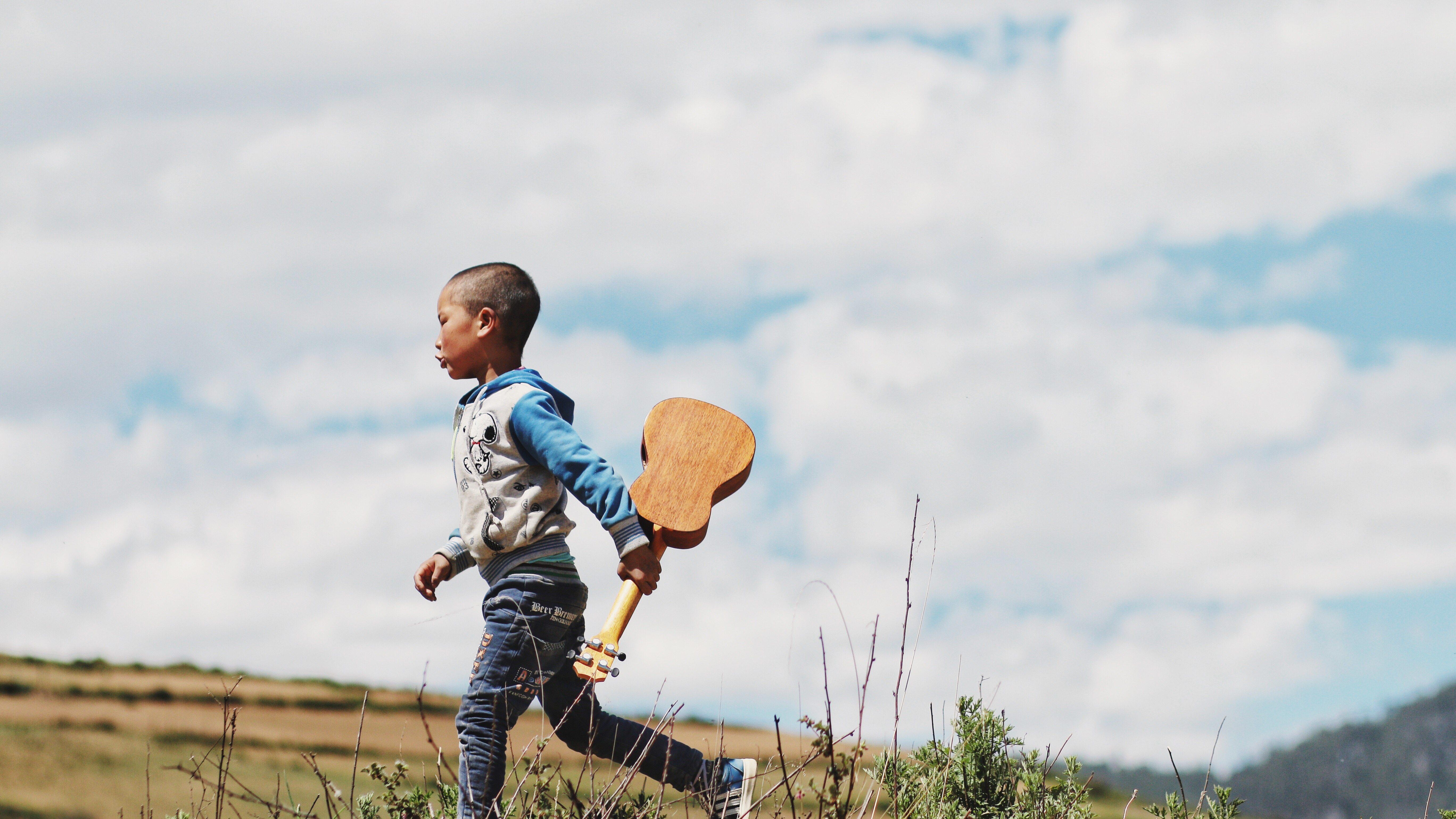 Niño camina con el ukulele